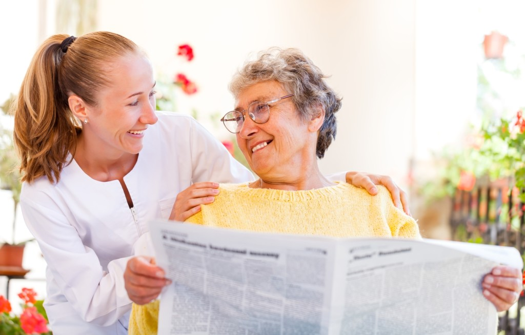 Caregiver reading newspaper web1